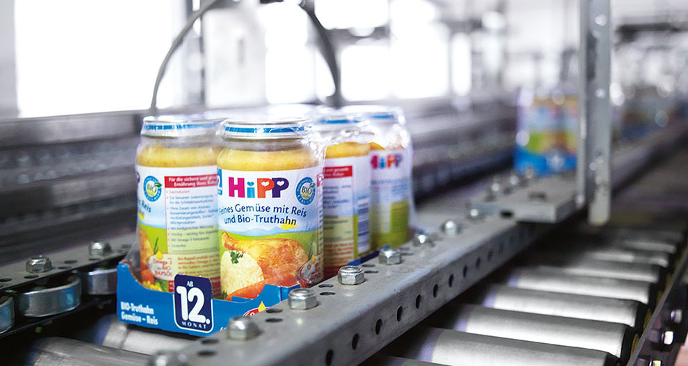 HiPP jar products wrapped together by sustainalbe plastic packaging on a supply belt inside a production factory.
