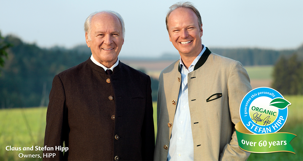 The owners of HiPP, Claus and Stefan Hipp, smiling and posing side by side with a green open field with some trees as the background